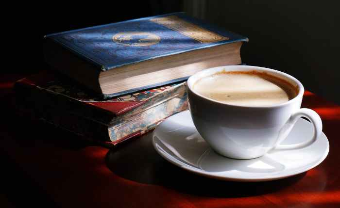 white teacup and saucer beside books